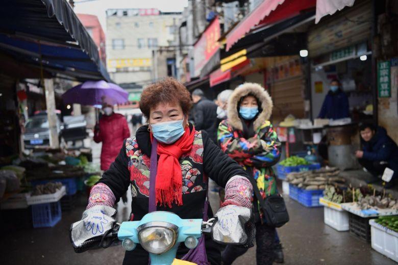 Một phụ nữ đi qua một khu chợ ở Vũ Hán hôm 24.1. Ảnh: AFP.
