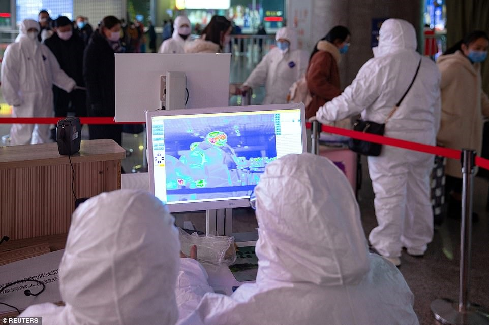 Kiểm tra nhiệt độ hành khách tại một nhà ga ở Nam Kinh, Trung Quốc. Ảnh: Reuters.