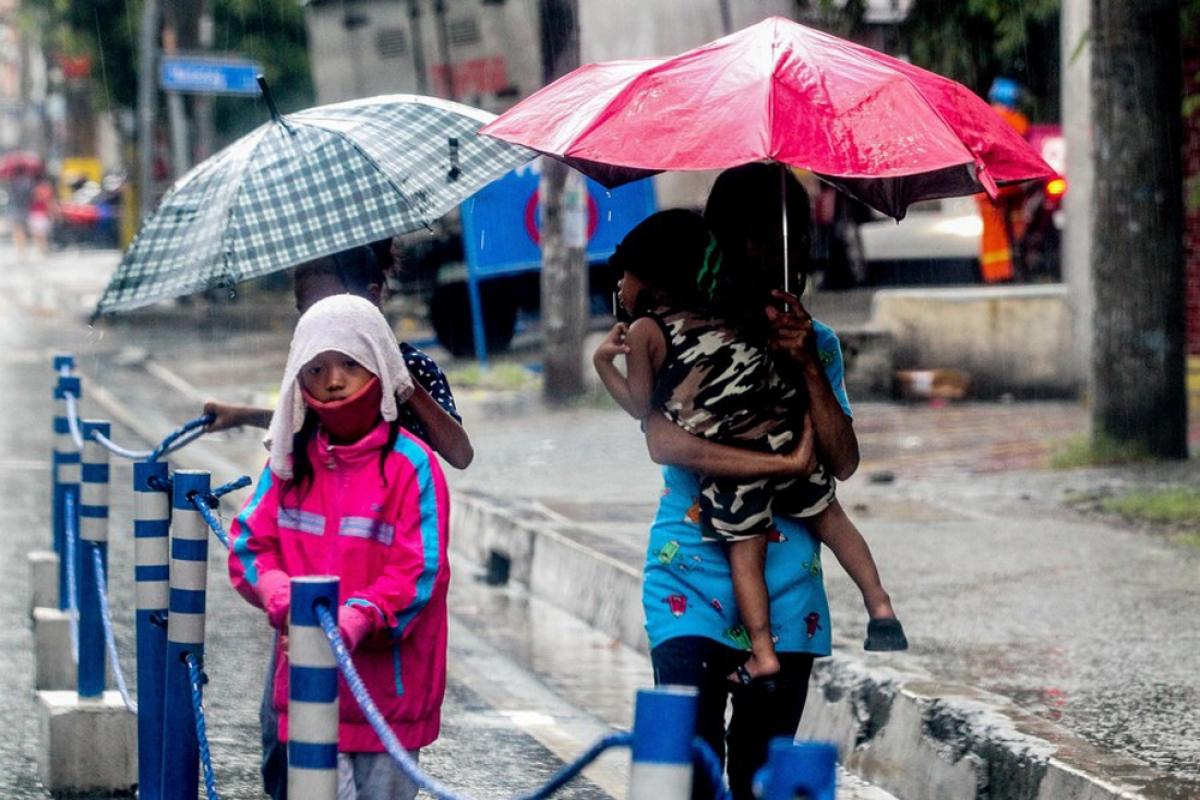 Một người phụ nữ cùng con nhỏ đang nhanh chóng về nhà khi bão Molave gây mưa lớn ở Manila ngày 25/10. Ảnh: Tân Hoa xã.