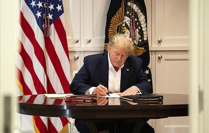 Tồng thống 74 tuổi ký giấy tờ khi làm việc ở Trung tâm Quân y Walter Reed hôm 3/10. Ảnh: EPA.